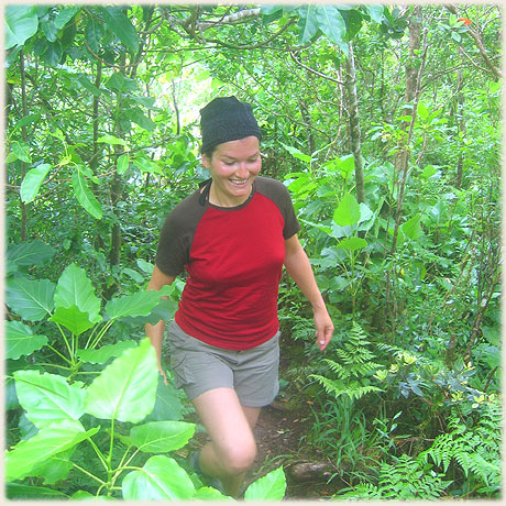 Sokala guest Evelyne makes her way up a luxuriant mountain track on Rarotonga's cross-island walk, guided by Pa's Cross Mountain Walk.